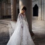 A bride wearing lace princess wedding dress with long flared sleeves.