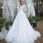 A bride wearing princess wedding dress with bodice decorated with lace and drapery and complex, multi-layered skirt with a long train.