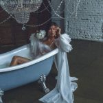 A bride sitting in a bath and wearing a white bridal robe with sleeves